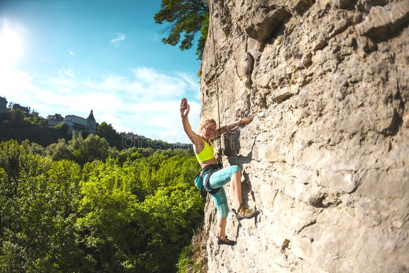 The woman gives five. The girl climbs the rock. A woman is engaged in fitness in nature. The climber gives five companions after overcoming the climbing route stock images
