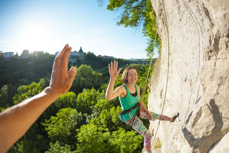 The woman gives five. The girl climbs the rock. A women is engaged in fitness in nature. The climber gives five companions after overcoming the climbing route royalty free stock images
