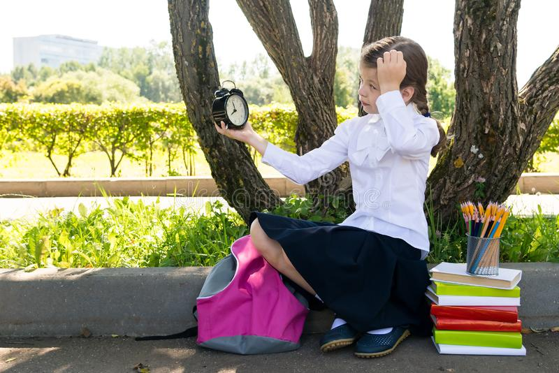 Girl with a clock thinks about school classes in the summer outside stock image