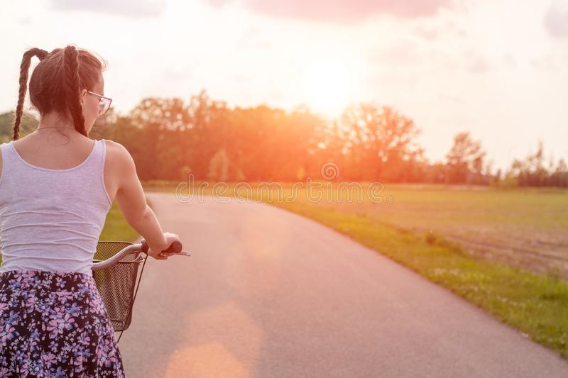 Girl close up with bike at the summer sunset on the road in the city park. Cycling down the street to work at summer sunset. royalty free stock image