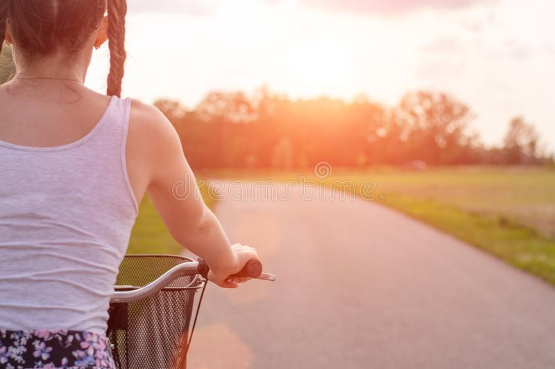 Girl close up with bike at the summer sunset on the road in the city park. Cycling down the street to work at summer sunset. stock photos