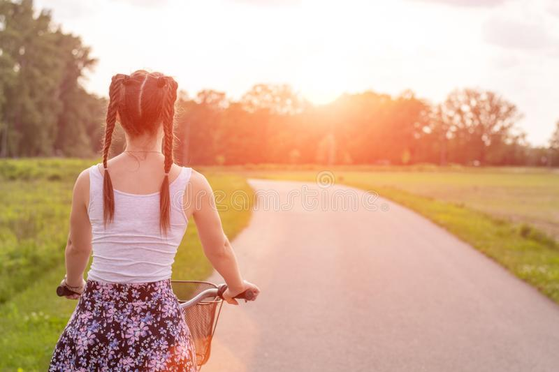 Girl close up with bike at the summer sunset on the road in the city park. Cycling down the street to work at summer sunset royalty free stock images