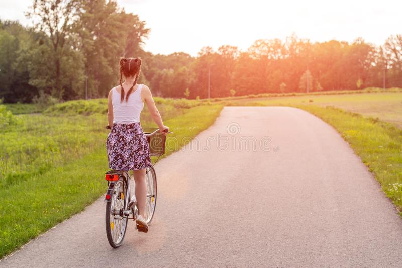 Girl close up with bike at the summer sunset on the road in the city park. Cycling down the street to work at summer sunset. stock photo