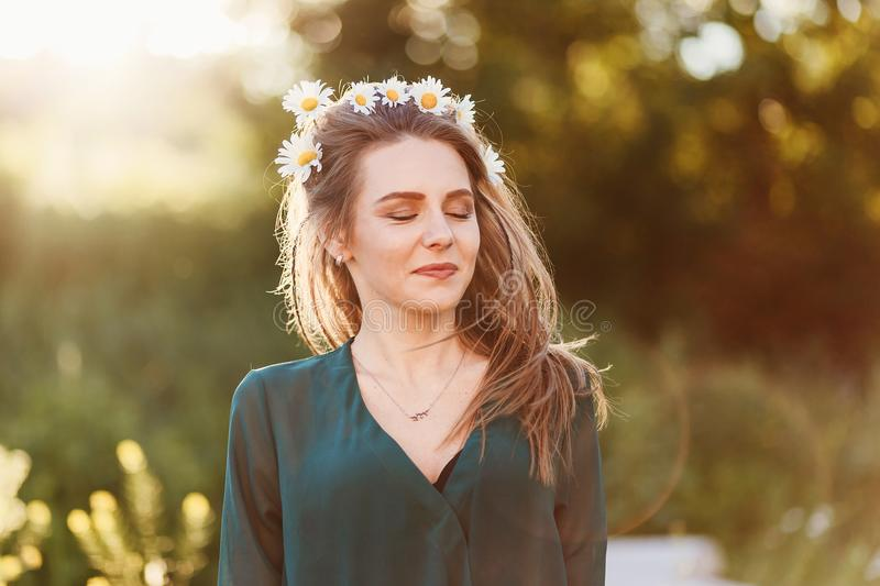 Girl with closed eyes with daisies on her head royalty free stock photography