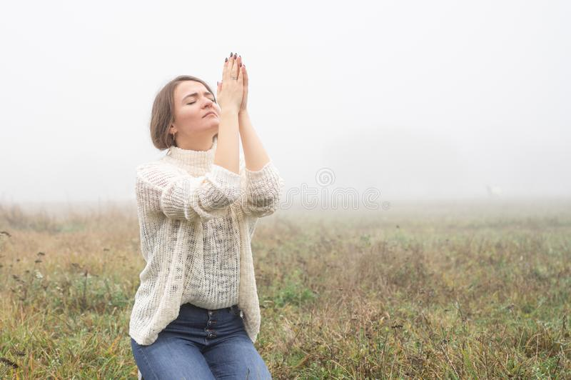Girl closed her eyes on the knees, praying in a field during beautiful fog. stock photography