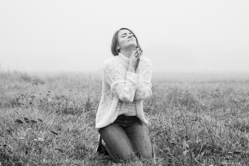 Girl closed her eyes on the knees, praying in a field during beautiful fog. stock image