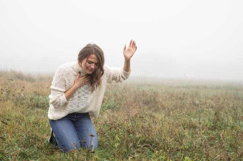 Girl closed her eyes on the knees, praying in a field during beautiful fog. stock photo