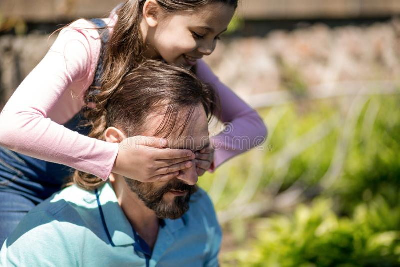 The Girl Is Closeing Her Dad`s Eyes With Her Hands Outdoors. stock images