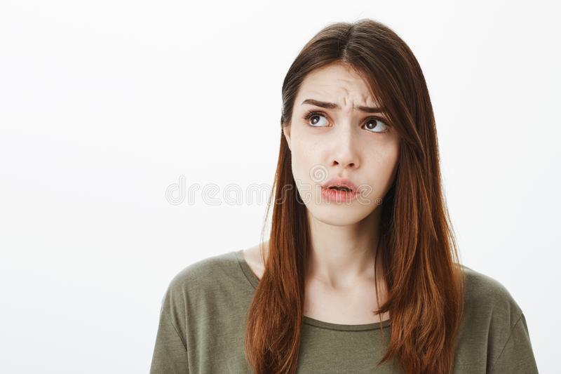 Girl cnannot focus, being intense because of large spider in corner of ceiling. Worried charming caucasian female royalty free stock images