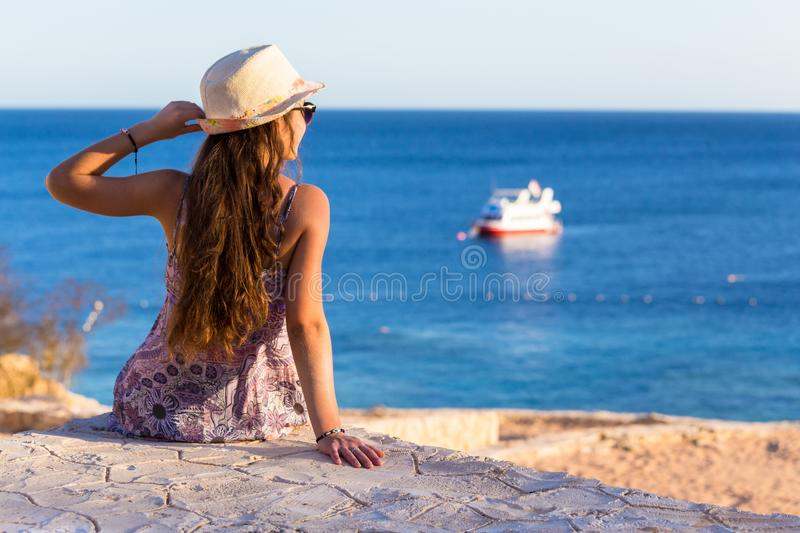 Girl on the coast looking to the boat at sea stock photos
