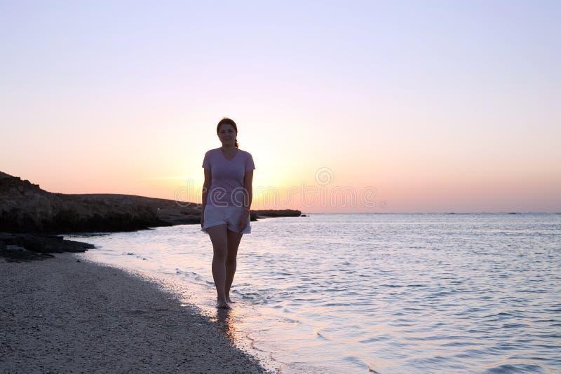Girl at coast sea  during  sunrise