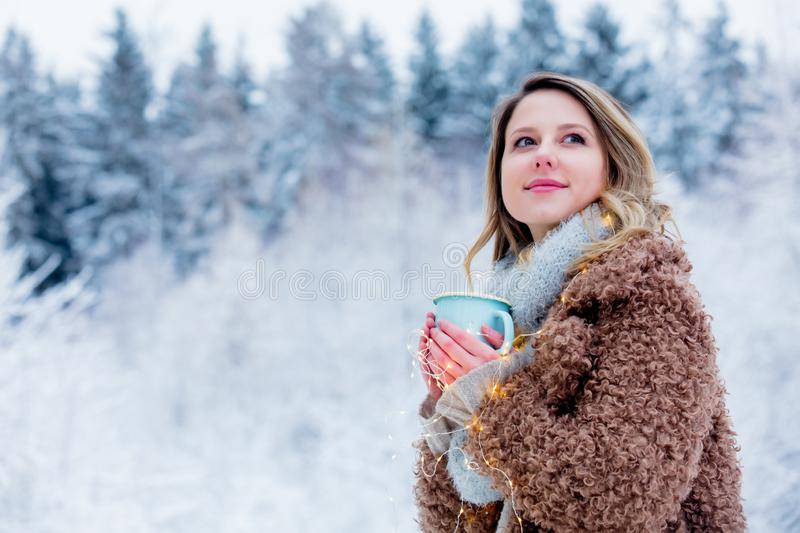 Girl in coat with cup of drink in a snow forest royalty free stock images
