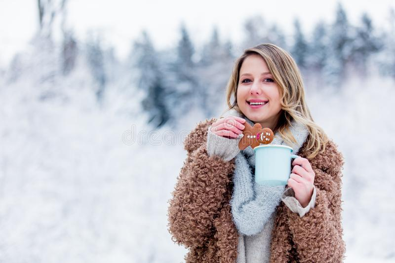 Girl in coat with cup of hot drink and cookie in a snow forest royalty free stock photos