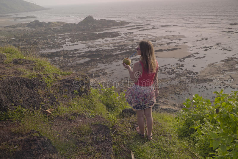 The girl with the coconut looks at the beautiful view stock photos