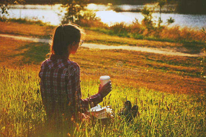 Girl with coffee cup and book. Enjoying on summer shore of river royalty free stock image