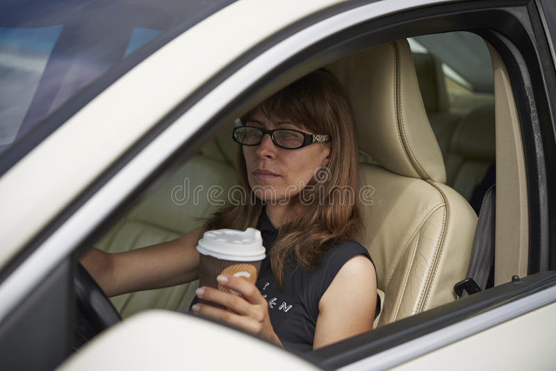 Girl with coffee in a white car royalty free stock images