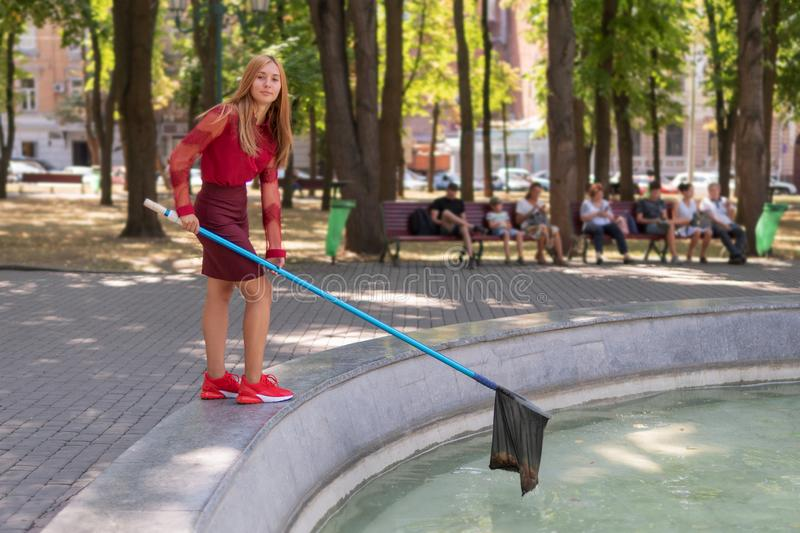 Girl collects trash from the water stock photography