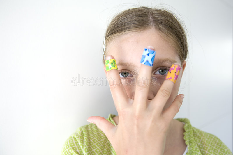 Girl with coloful adhesive plasters on her fingers royalty free stock photo