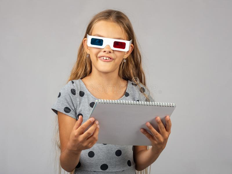 The girl in the colored 3D glasses, made using the anaglyph technology of the 3D glasses, looked into the frame. The girl in the colored 3D glasses, made using royalty free stock photos