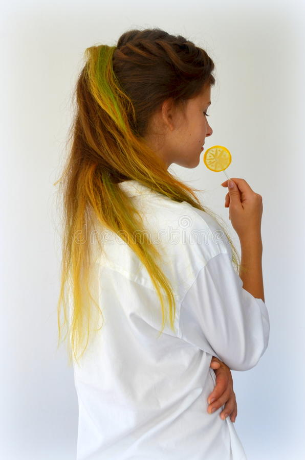Girl with colored strands and with a lollipop. Girl with long hair dyed with colored strands Ombre royalty free stock image