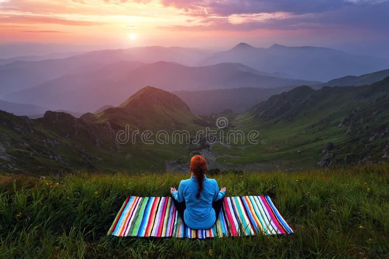 The girl on colorful mat is practicing Yoga. Beautiful mesmerising sunrise, orange sky with clouds, high mountains in fog. Summer. The girl on colorful mat is royalty free stock image