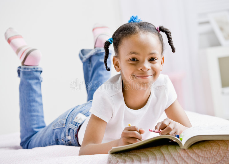 Girl coloring in coloring book royalty free stock images