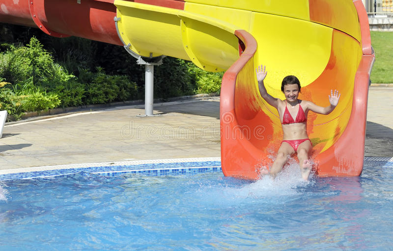 Girl comes down the slide into the pool. In summer time royalty free stock image