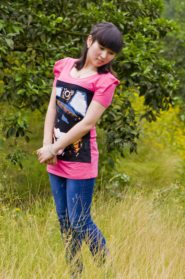 Girl with comfortable position. A chinese girl was standing in the citrus orchard using a comfortable position which with full of yellow weeds and sweet smiling stock images