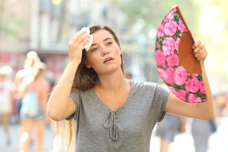 Girl complaining suffering heat stroke. Front view portrait of a overwhelmed girl complaining suffering heat stroke in the street on summer royalty free stock photos