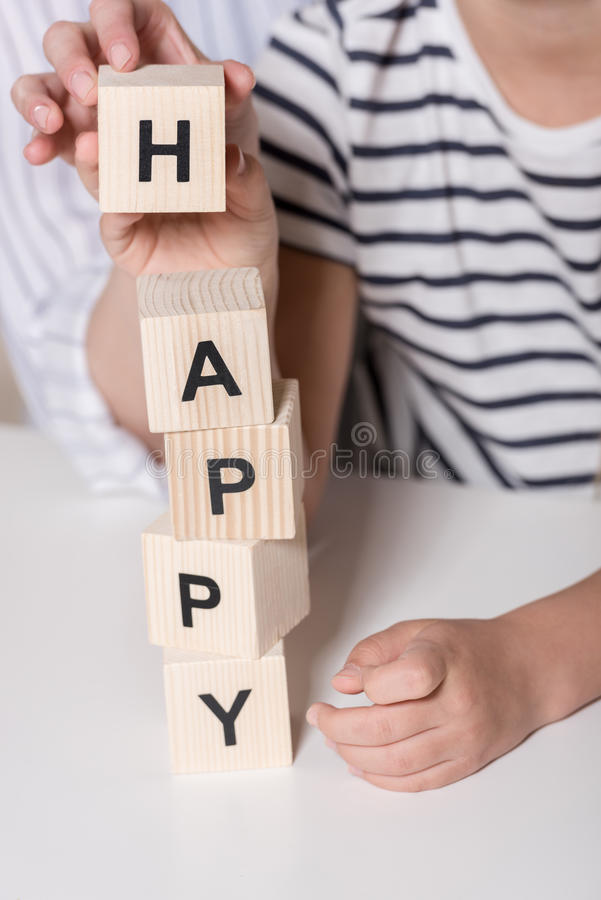 Girl composing word Happy. Using wooden cubes royalty free stock photo