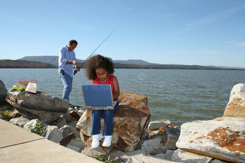 Girl on computer and fishing royalty free stock photo
