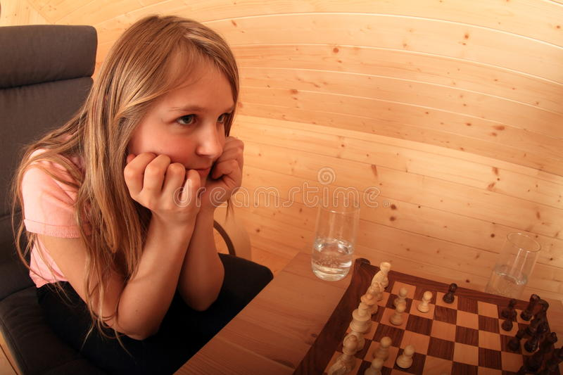 Girl concentrated for next move in chess. Blond Caucasian kid - young hairy girl sitting on armchair and concentrating for next move in chess in wooden attic royalty free stock photos