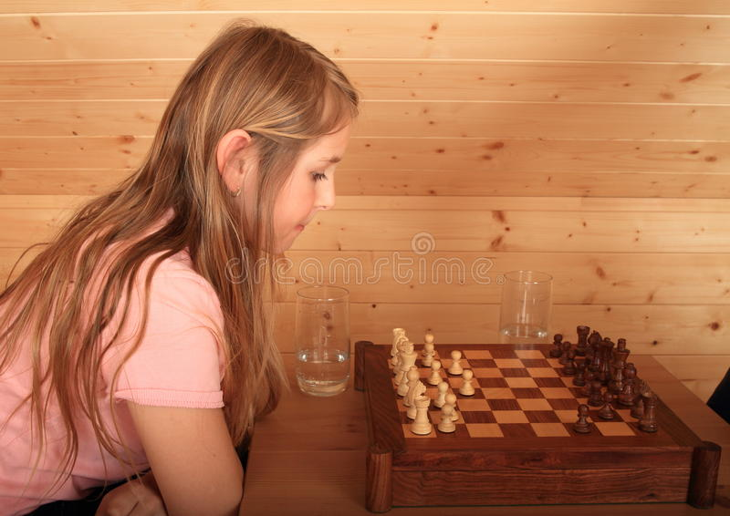 Girl concentrated for next move in chess. Blond Caucasian kid - young hairy girl sitting on armchair and concentrating for next move in chess in wooden attic royalty free stock image