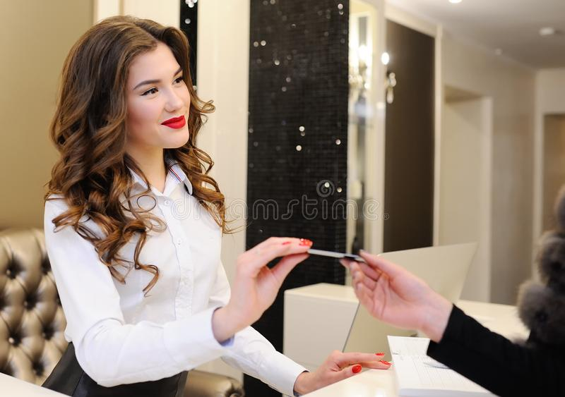Girl consultant gives a discount card to the client royalty free stock photography