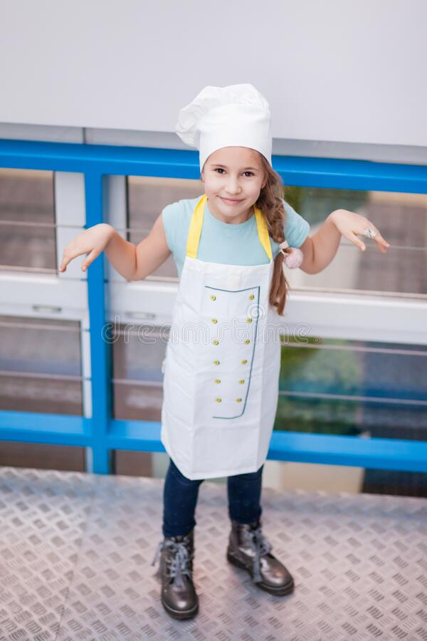 Girl in a cook suit stands on a gray background and raised her hands to the sides royalty free stock photography