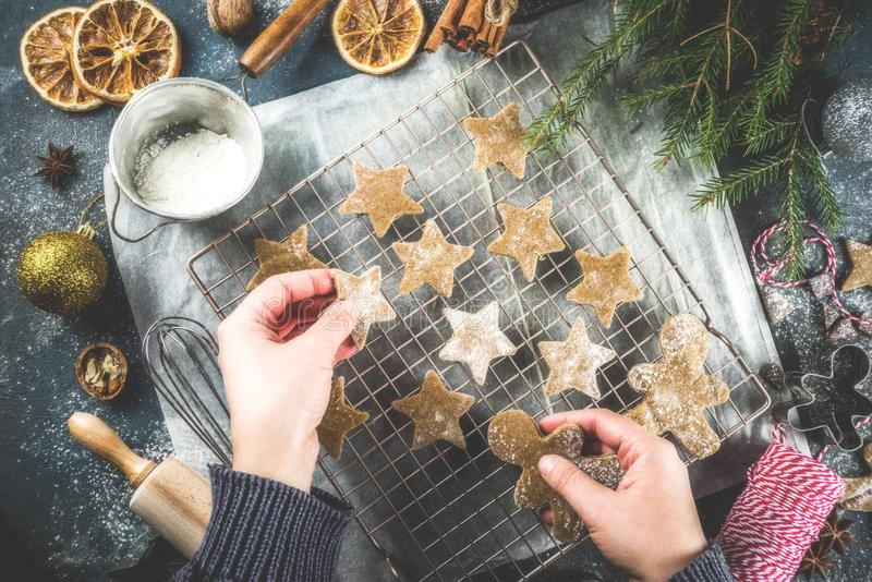 Making gingerbread cookie. Girl cooking christmas homemade gingerbread star cookies, gingerbread men, flat lay, top view, with accessories ingredients for baking stock photography