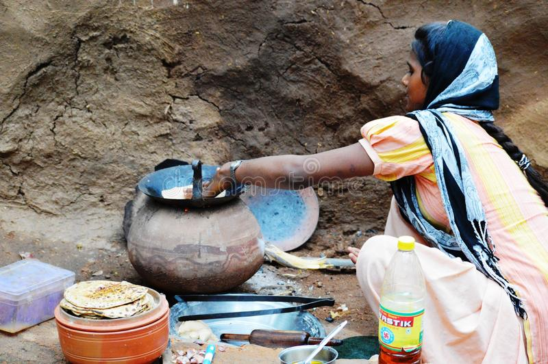 Girl Cooking Food In Village. Indian girl cooking food with traditional way of baking chapati on wood fire stove chulha at Indian Village in Udaipur, India
