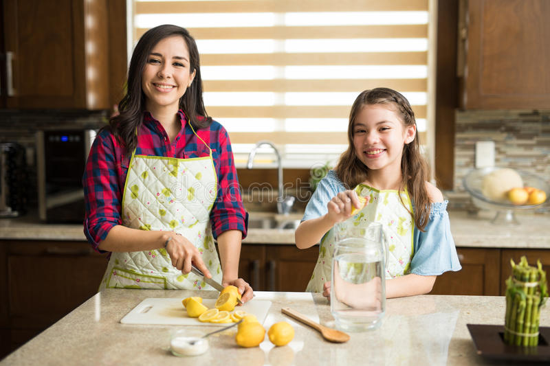Girl cooking with her mom at home royalty free stock images
