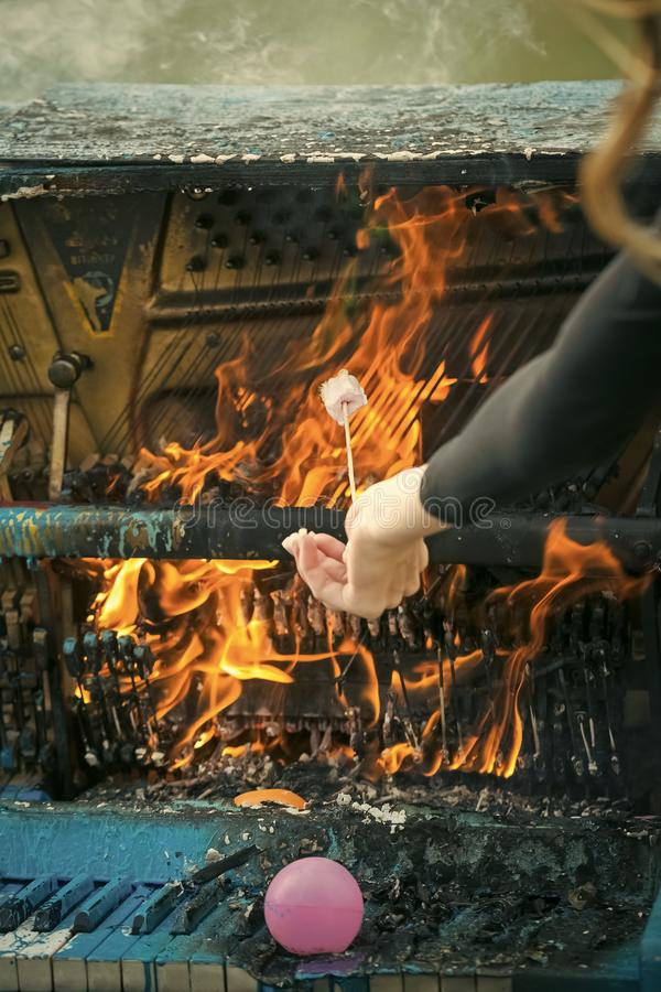 Girl is cooking marshmallows on burning piano on fire royalty free stock photos