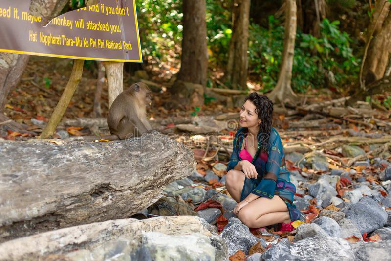 A girl in a cool swimsuit and pareo talking to monkeys on a tropical monkey beach stock photography