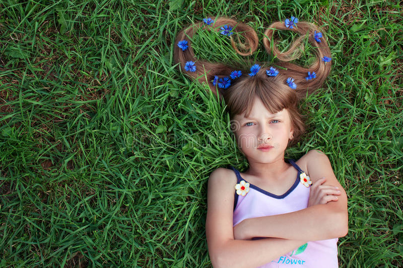 Girl with cornflowers in her hair and folded arms. Girl with cornflowers in her long hair lying on the grass, folded arms and making grimace royalty free stock images
