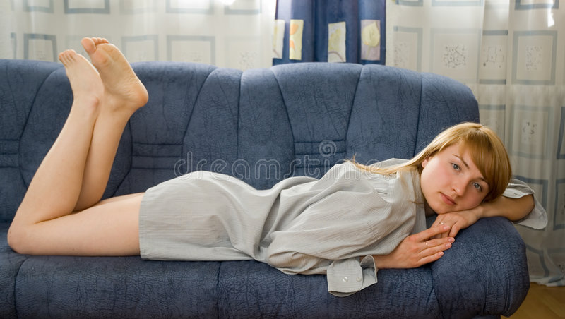 Girl on the couch. Young pretty woman on blue couch stock photos