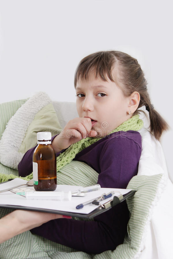 Girl coughing and lying in bed with medicine. Ill girl coughing and lying in bed with medicine royalty free stock photography