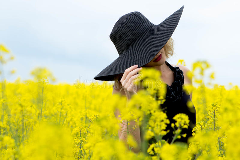 The girl covered her face with a hat in the field with flowers. The girl covered her face with a hat in a field with yellow flowers stock photos
