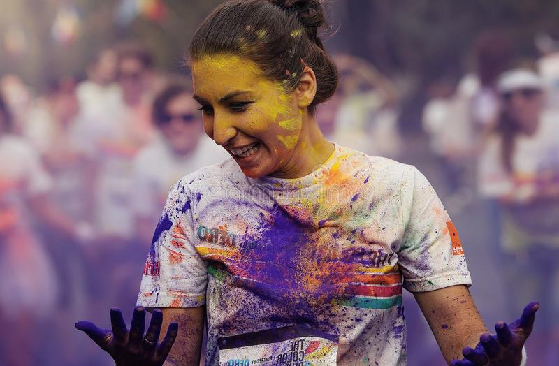 Woman at Color Run Bucharest. Girl covered with yellow, blue and orange powder. Women with brightly colored face, happy and smiling. People blurred background
