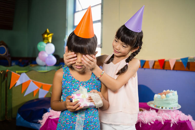 Girl covering birthday girls eyes and offering a gift royalty free stock photos