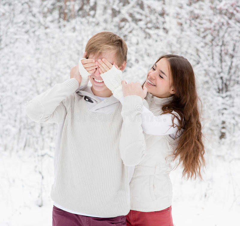 Girl covering boyfriends eyes with hands.  royalty free stock images