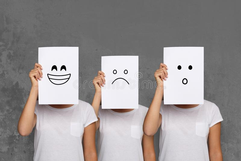 Girl covering face with white boards. Set of painted emotions royalty free stock images