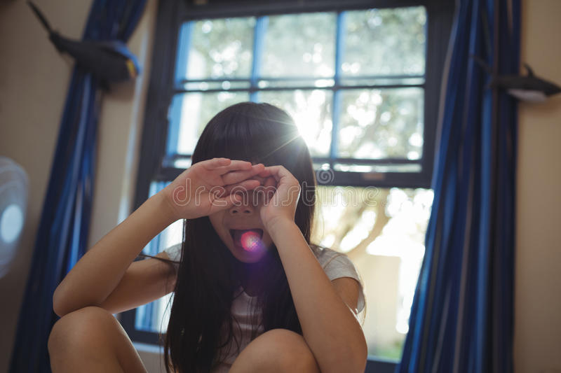 Girl covering her eyes in the bed room stock photography