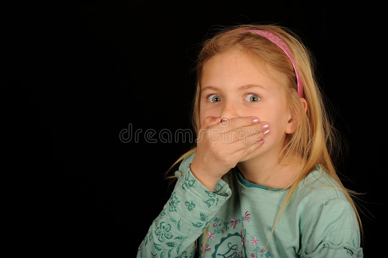 Girl covering mouth. Half body portrait of cute young girl with hand over mouth, black background royalty free stock photo